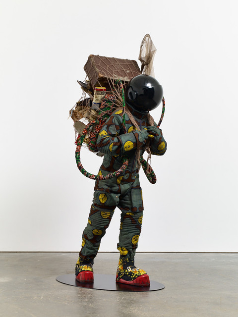 Refugee Astronaut, 2015 Fibreglass mannequin, Dutch wax printed cotton textile, net, possessions, astronaut helmet, moon boots and steel baseplate 81 9/10 × 36 3/5 × 35 2/5 in 208 × 93 × 90 cm James Cohan Gallery
